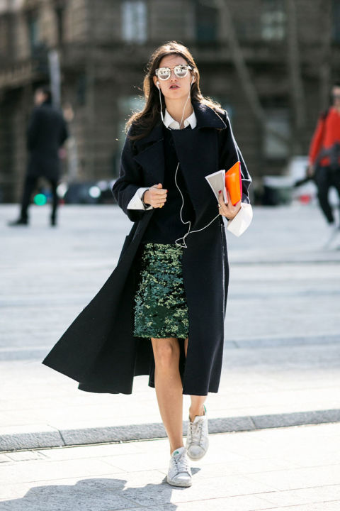 adidas sneakers-white sneakers-emerald green sequined skirt-sweater over collared shirt-cuffs-black coat-model off duty style-milan fashion week street style-